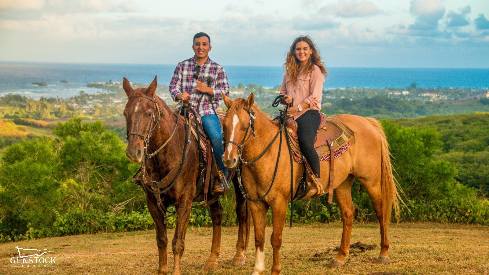 Couple riding horses at sunset in Hawaii