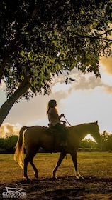 Woman riding a horse at sunset in Hawaii