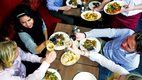 Group of people having meal at restaurant while on food tour in Galway
