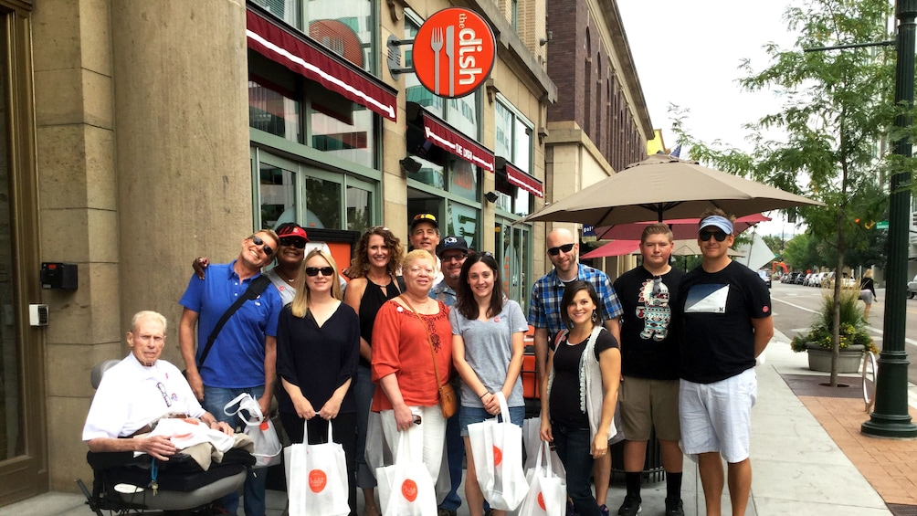 Show item 1 of 5. Group stands in front of restaurant on food tour in Boise