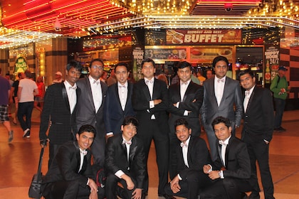A group of men wearing suits pose for a picture outside a Las Vegas Casino