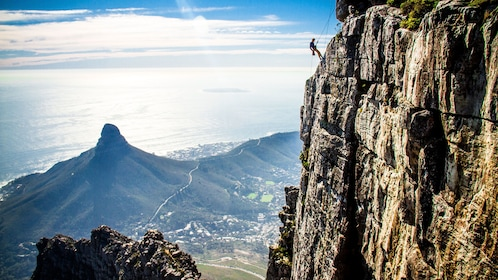 Person solo abseiling down cliff face of Table Mountain in Cape Town