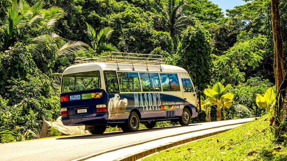 Show item 1 of 5. Tour bus traveling up street in Mahe Island