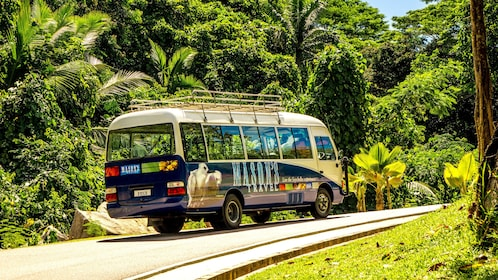 Tour bus traveling up street in Mahe Island