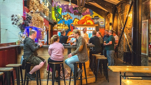 Group of people drinking pints of beer in a colorful brewery in York