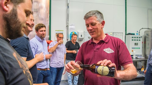 Brewmaster pours a beer into a glass for a tour group