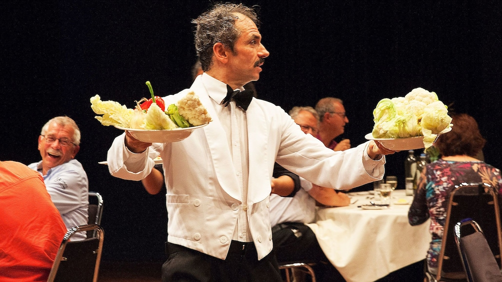 Show item 2 of 5. Actor carries food through audience during Faulty Towers show in London