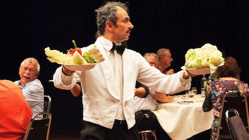 Actor carries food through audience during Faulty Towers show in London