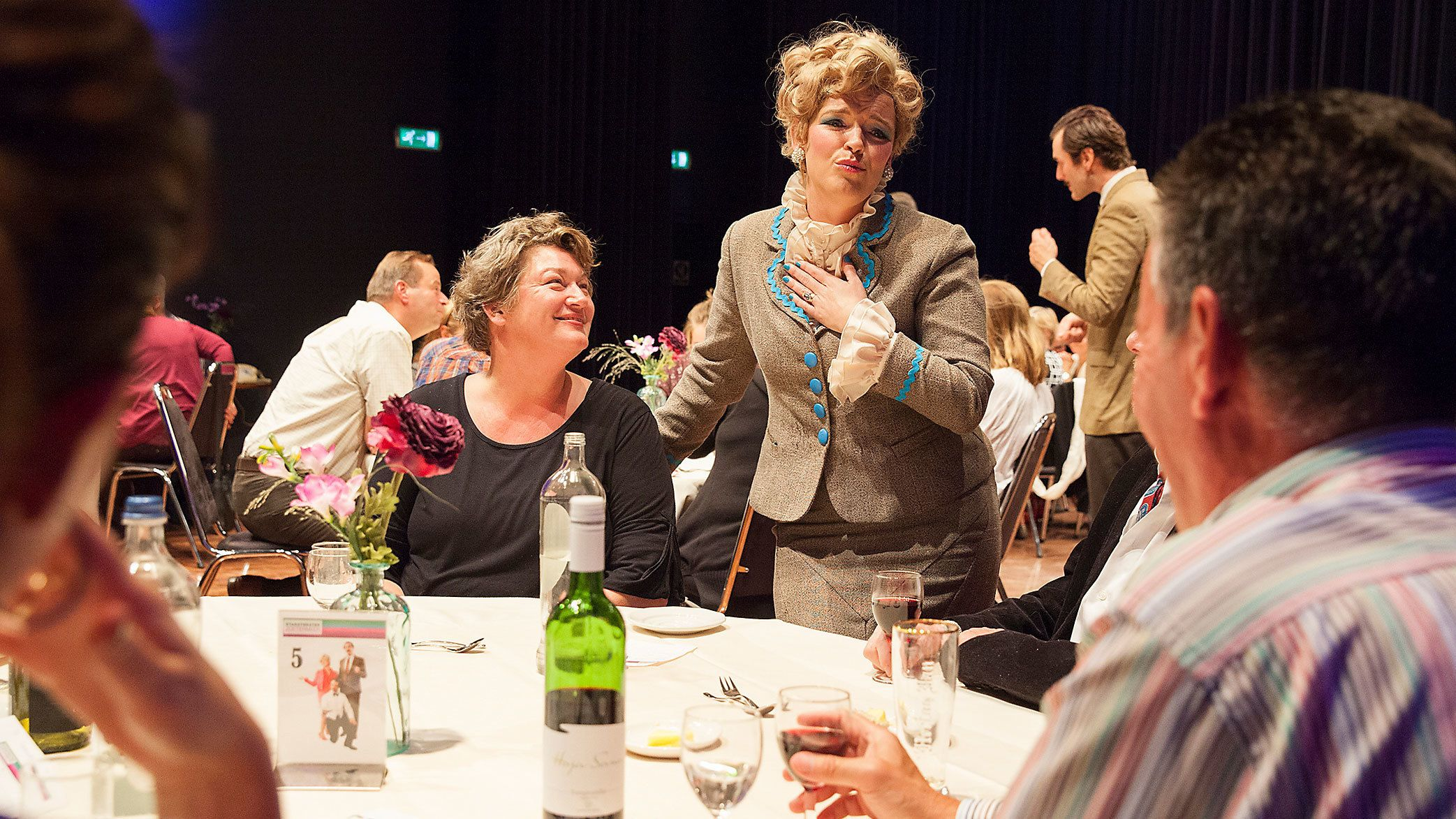 Actress socializing with dinner guests during Faulty Tower in Edinburgh