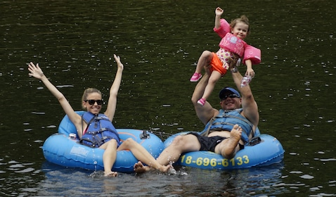 Family floating on tubes on a lake