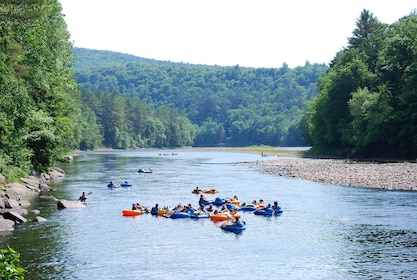 Group of people float a river on tubes with Kayakers