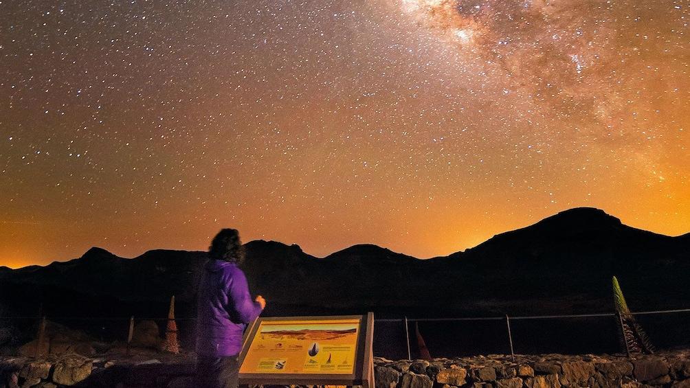 Foto 5 van 4. Woman looking up at the stars over Teide volcano