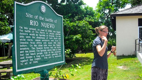 Tour guide stands next to a sign commemorating the battle of Rio Nuevo