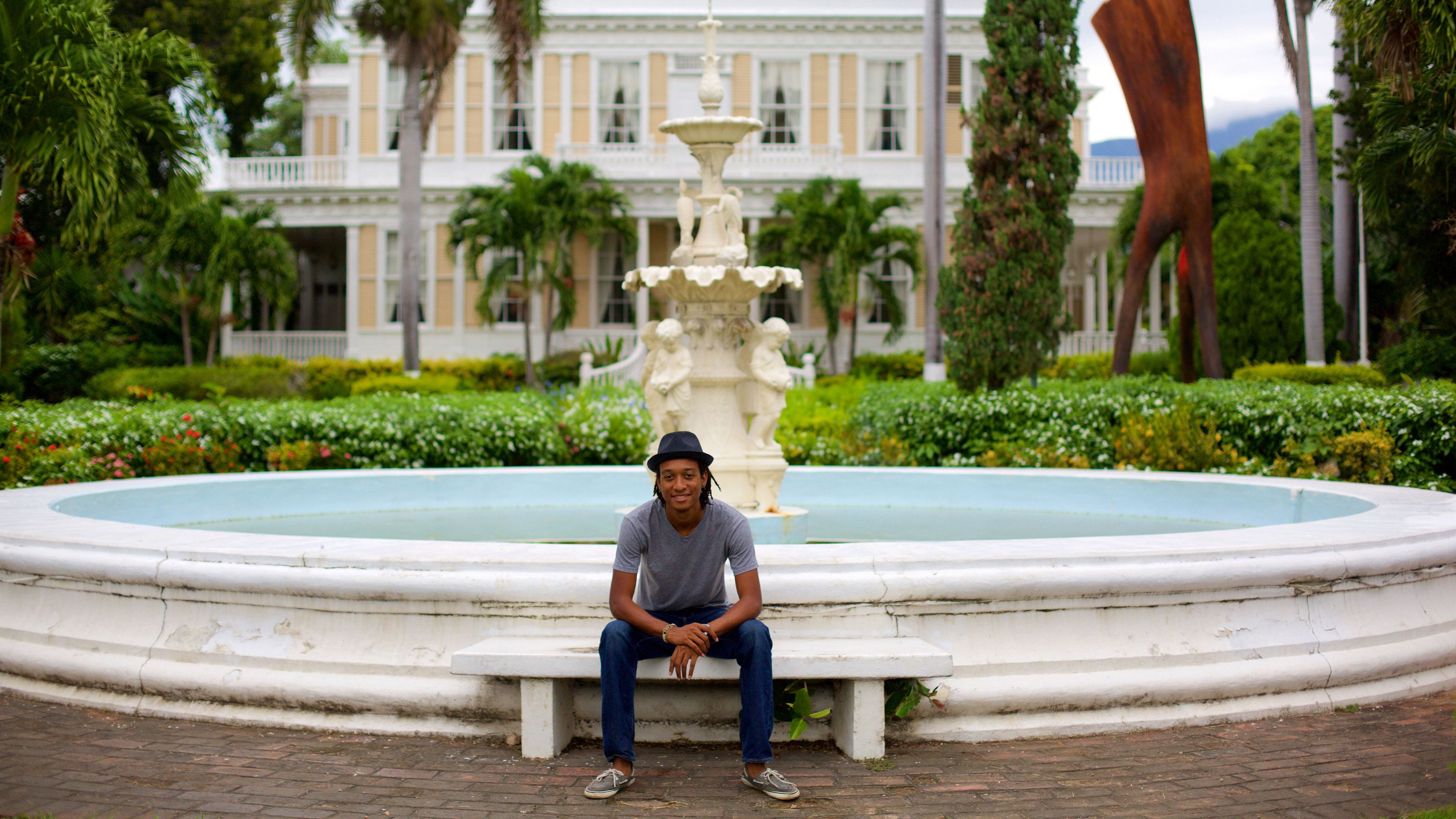 Man sitting in front of fountain at Devon House in Jamaica