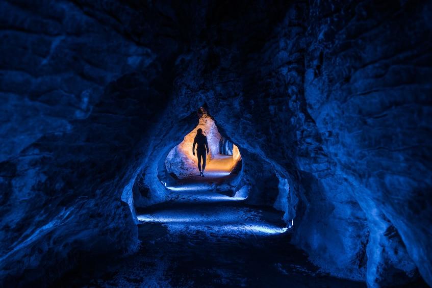 Show item 5 of 8. Person exploring Ruakuri Cave in New Zealand