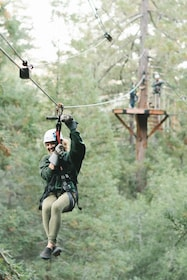 Woman holding onto harness as she ziplines from one tree to another in Sonoma County