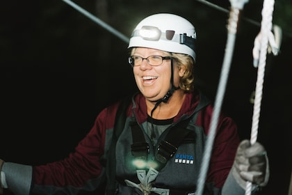 Woman smiling on the ziplining adventure at night in the Redwoods of Sonoma County