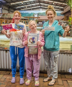 Girls hold up prints for World Ocean Day at Irukandji Shark and Ray Encounters