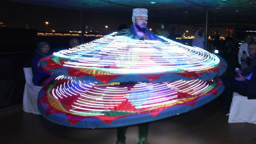 Show item 7 of 7. Performer with clothing with light in middle of performance during dinner cruise in Dubai