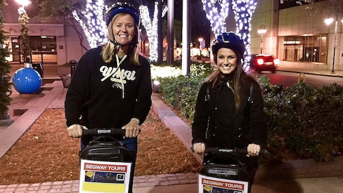 Two women on segways touring Houston in the evening