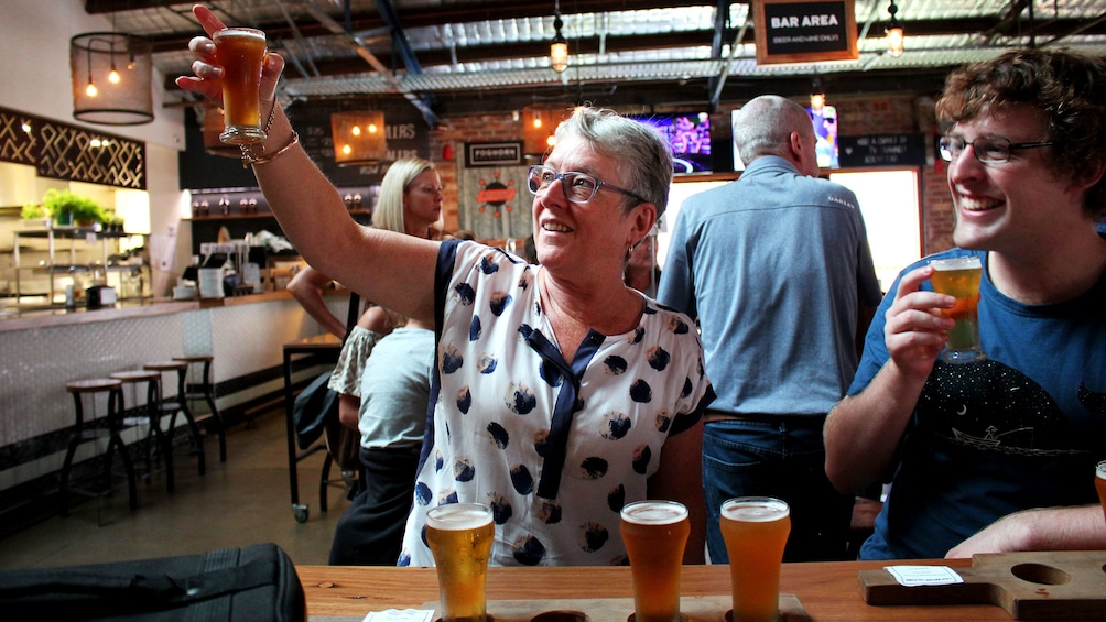 Woman looking at beer during pub walk in Sydney