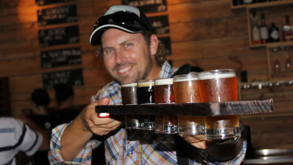 Man holding up flight of beer in Canberra