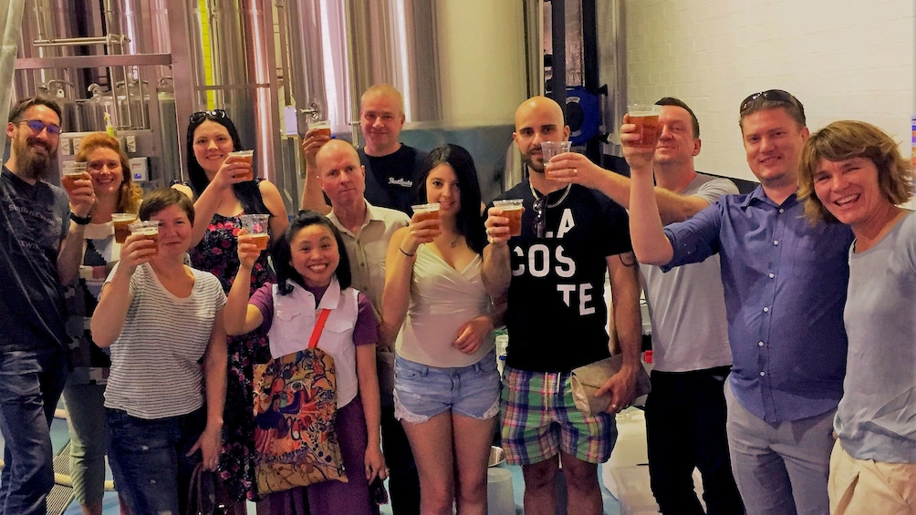 Tour group raising glasses of beer at the end of tour in brewery in Canberra