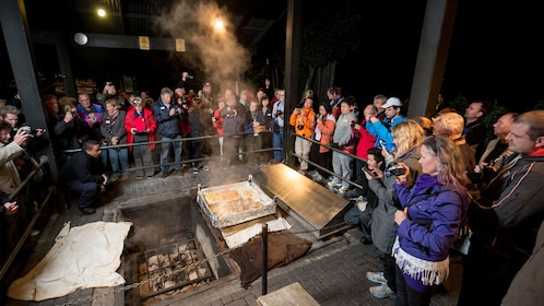 Tour group gathered around steam box cooking station in Rotorua