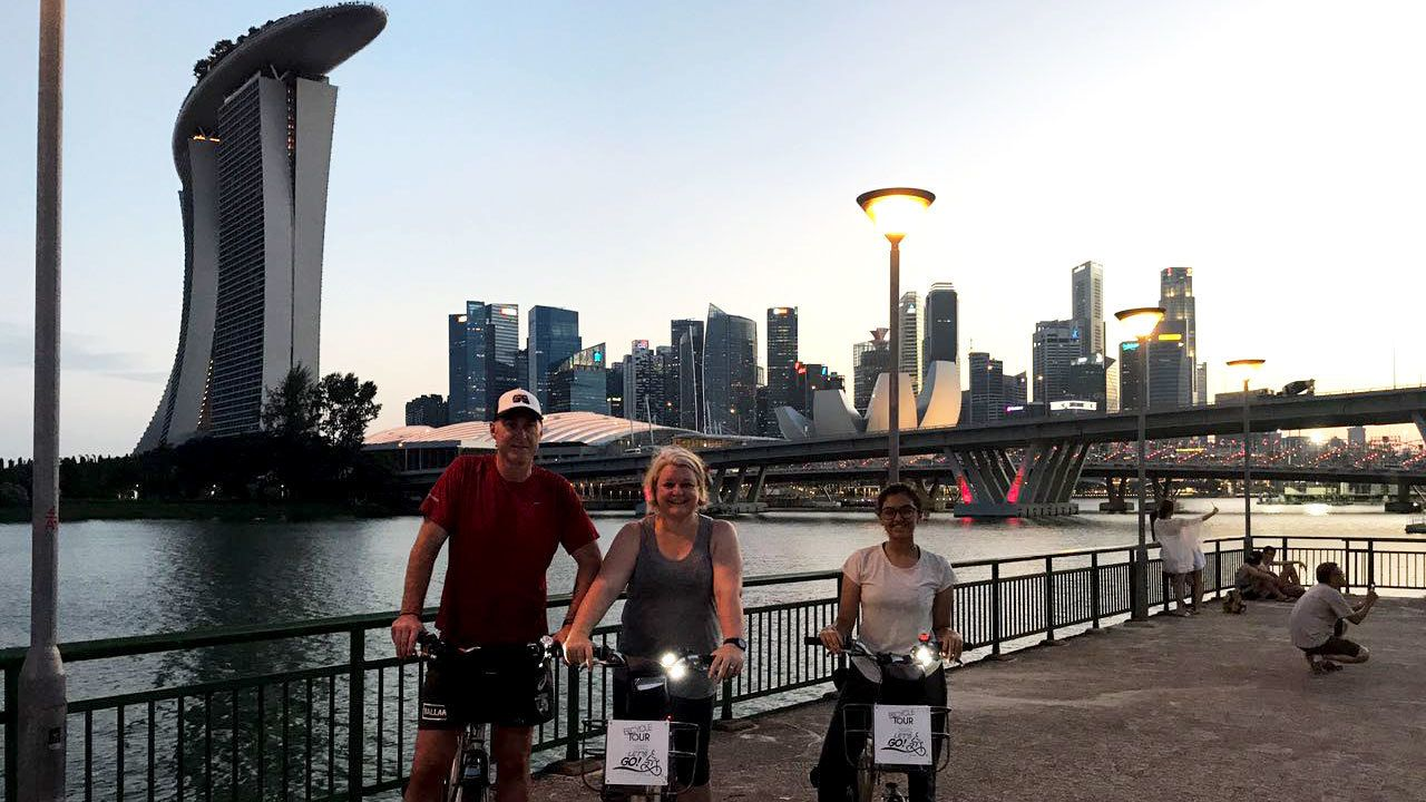 Trio on bikes on boardwalk to Marina Bay in Singapore