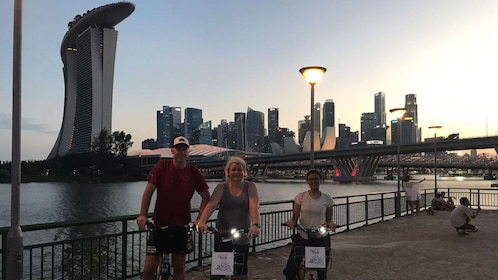 Trio on bikes at dusk in Singapore