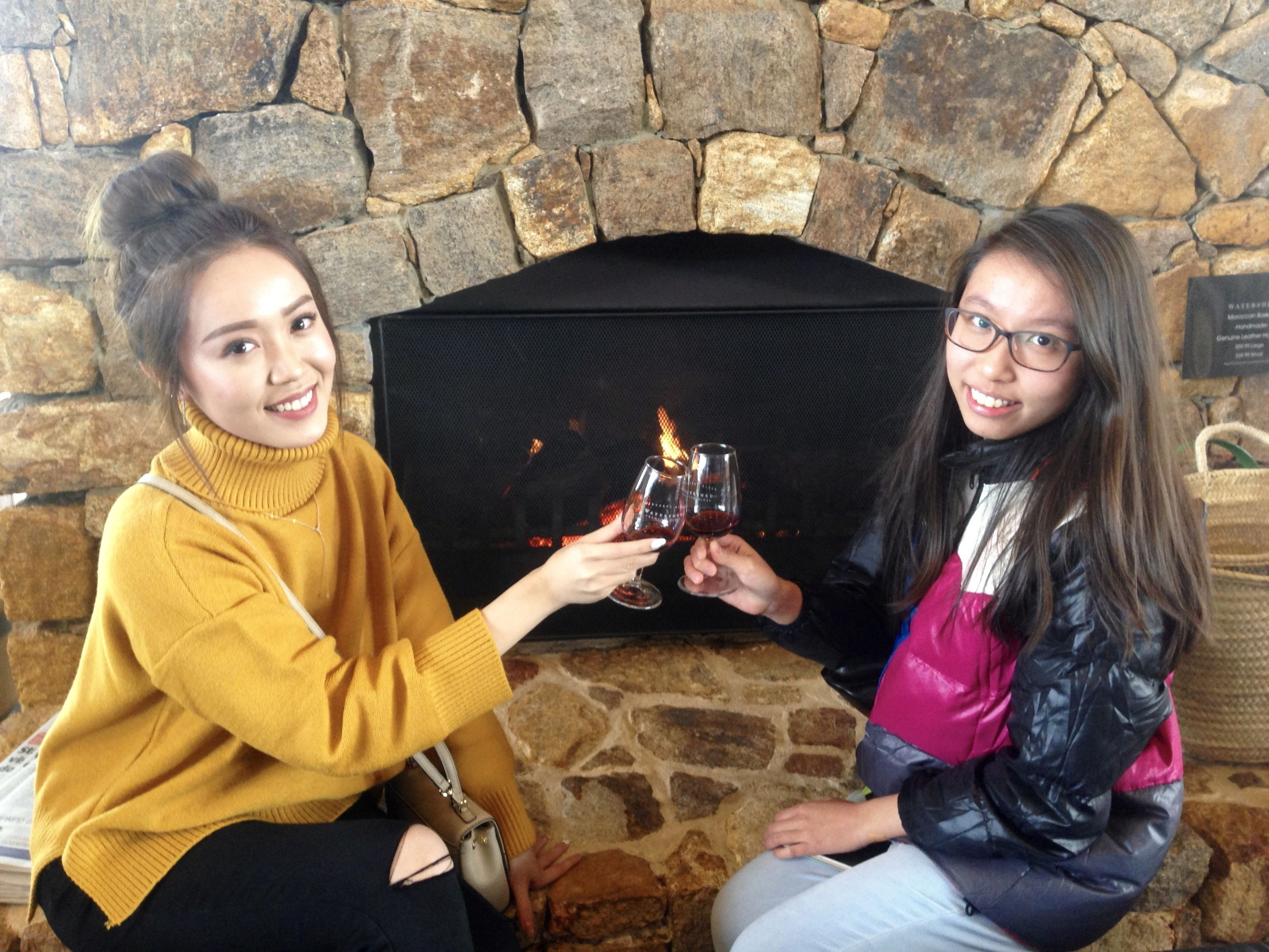 Two women toast with wine glasses next to a fire place