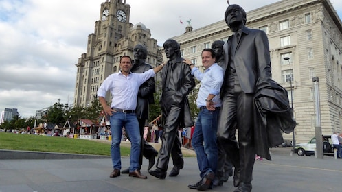 Tourists posing with Beatles statues in Liverpool