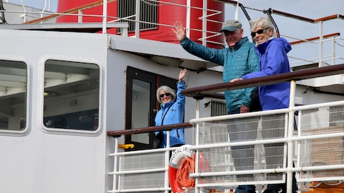 People waving from the deck of a boat in Liverpool