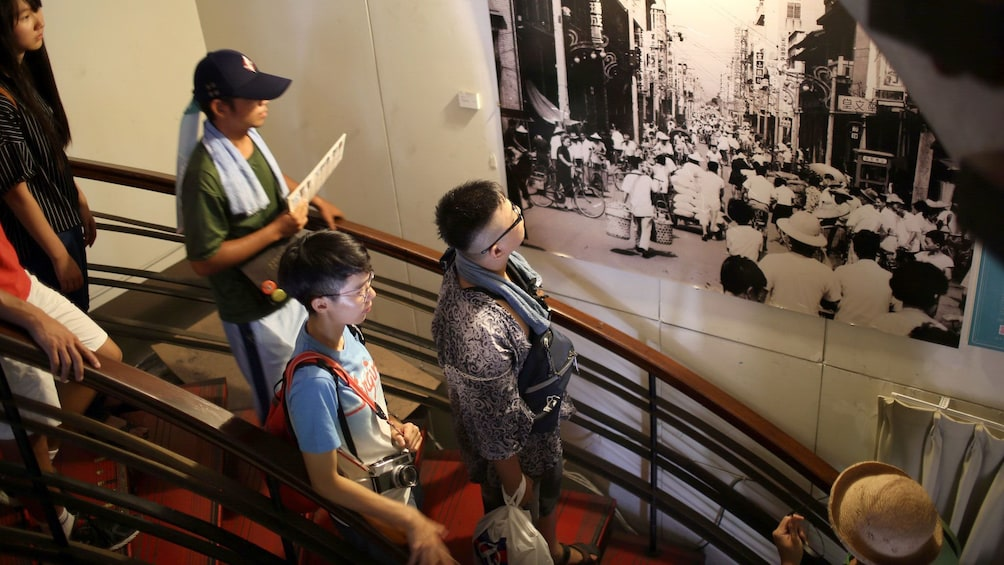 Show item 3 of 5. Tour group looking at historical photographs in Taichung