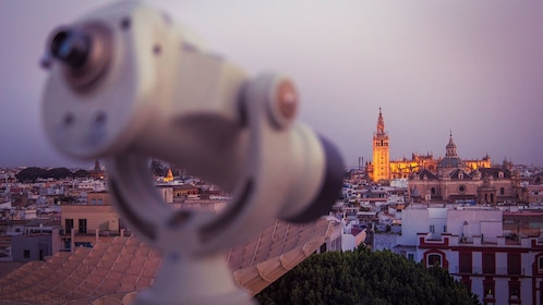 View of rooftops and cathedral ion Seville with spotting glass in foreground