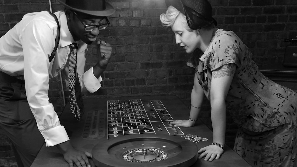 Show item 1 of 6. Black and white image of people in vintage clothing looking at a roulette table