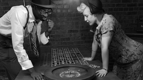 Black and white image of people in vintage clothing looking at a roulette table