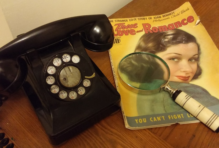 Show item 3 of 6. A rotary phone, old magazine and magnifying glass