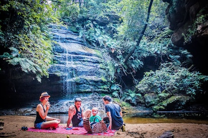 Family enjoying a picnic next to a waterfall in Australia