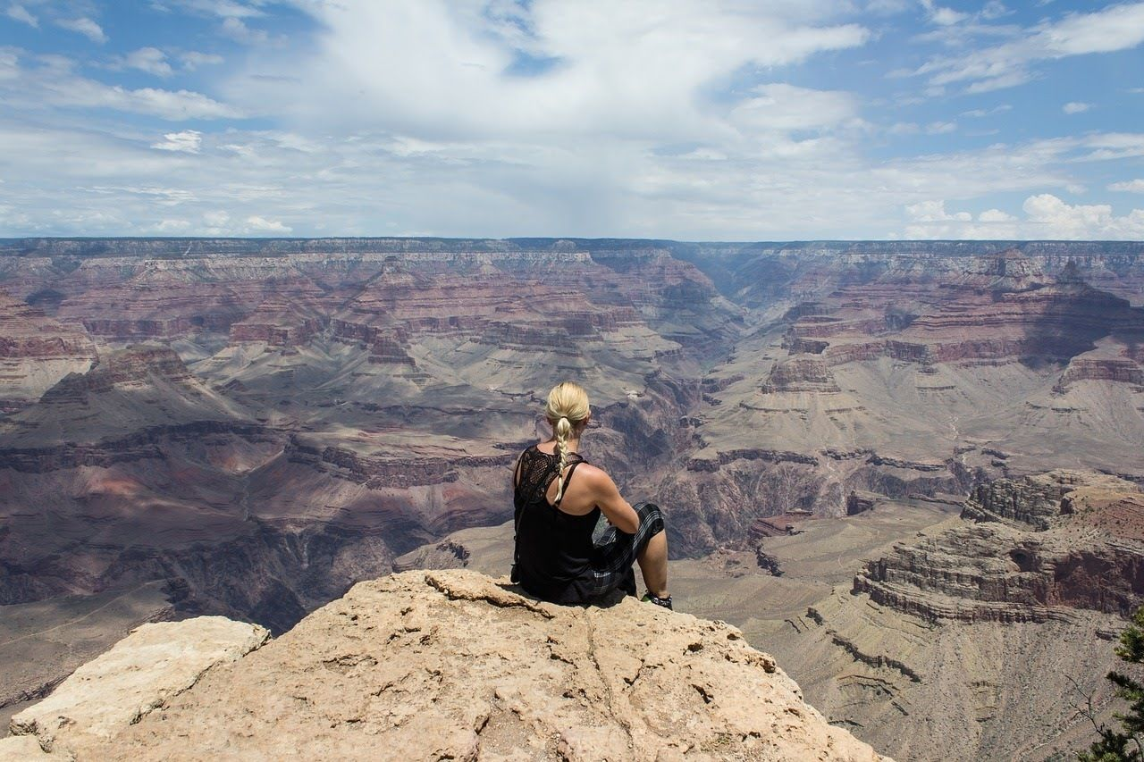 Woman sits on the edge of the Grand Canyon