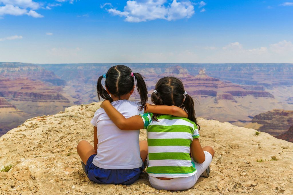 Two girls sit on the edge of the Grand Canyon