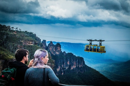 A couple taking in the views of the Three Sisters on a cloudy day in Australia