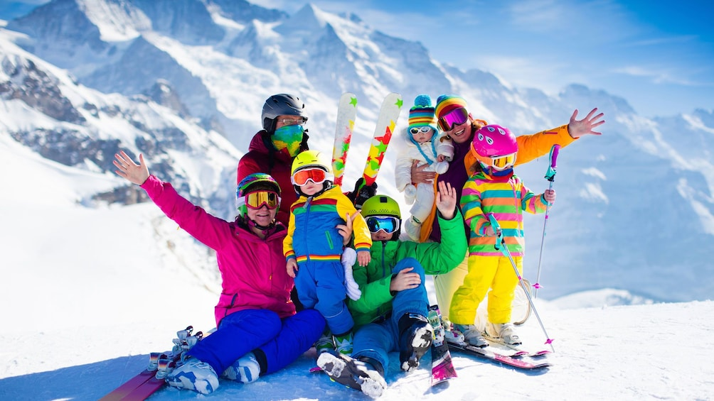 Show item 3 of 4. Group of brightly dressed skiers on slopes of Mammoth mountain in California