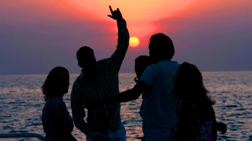 Four silhouetted people dance on a boat at sunset in Jamaica