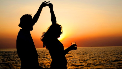 Two silhouetted people dance on a boat at sunset in Jamaica
