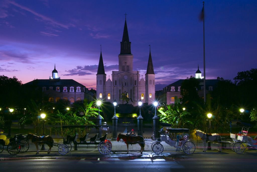 Horse drawn carriages next to Jackson Square at dusk