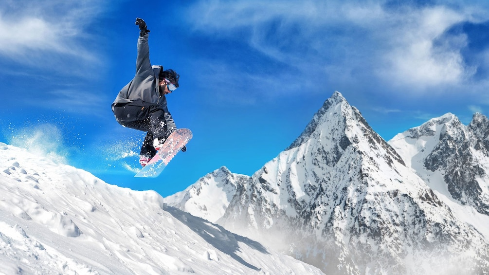 Show item 2 of 4. Man on snowboard in mid jump on slopes in Mammoth Lakes, California