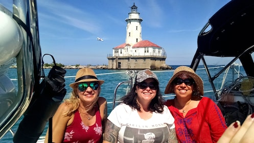 Trio of women smiling on boat in front of lighthouse