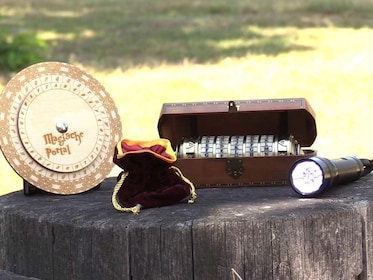 A flashlight, a velvet sack, and two codebreaking devices on a stump for a scavenger hunt