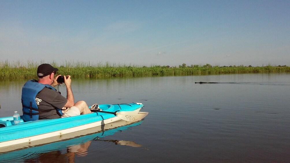 Show item 2 of 4. Man taking photos on the Delta Wildlife Kayak Tour